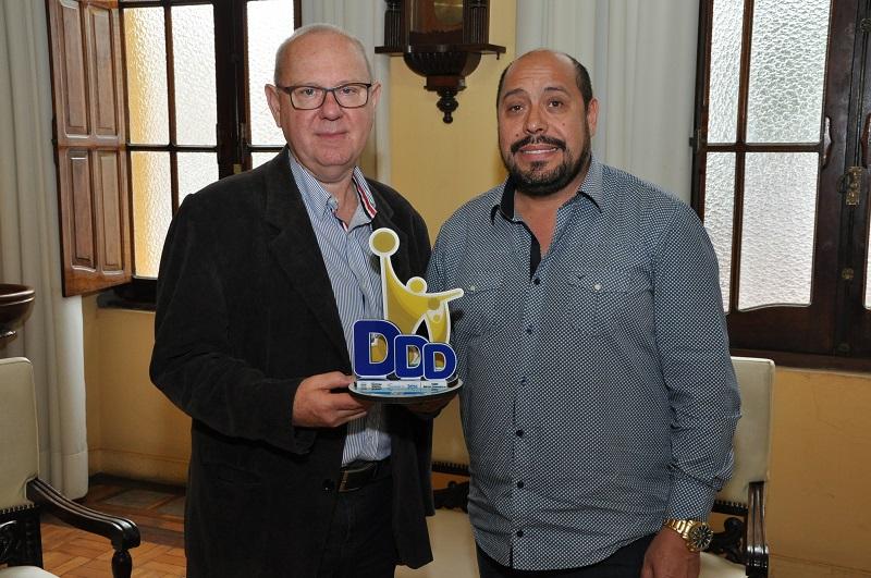 Celso (D) recebe o trófeu Mérito Comunitário das mãos de Perobelli