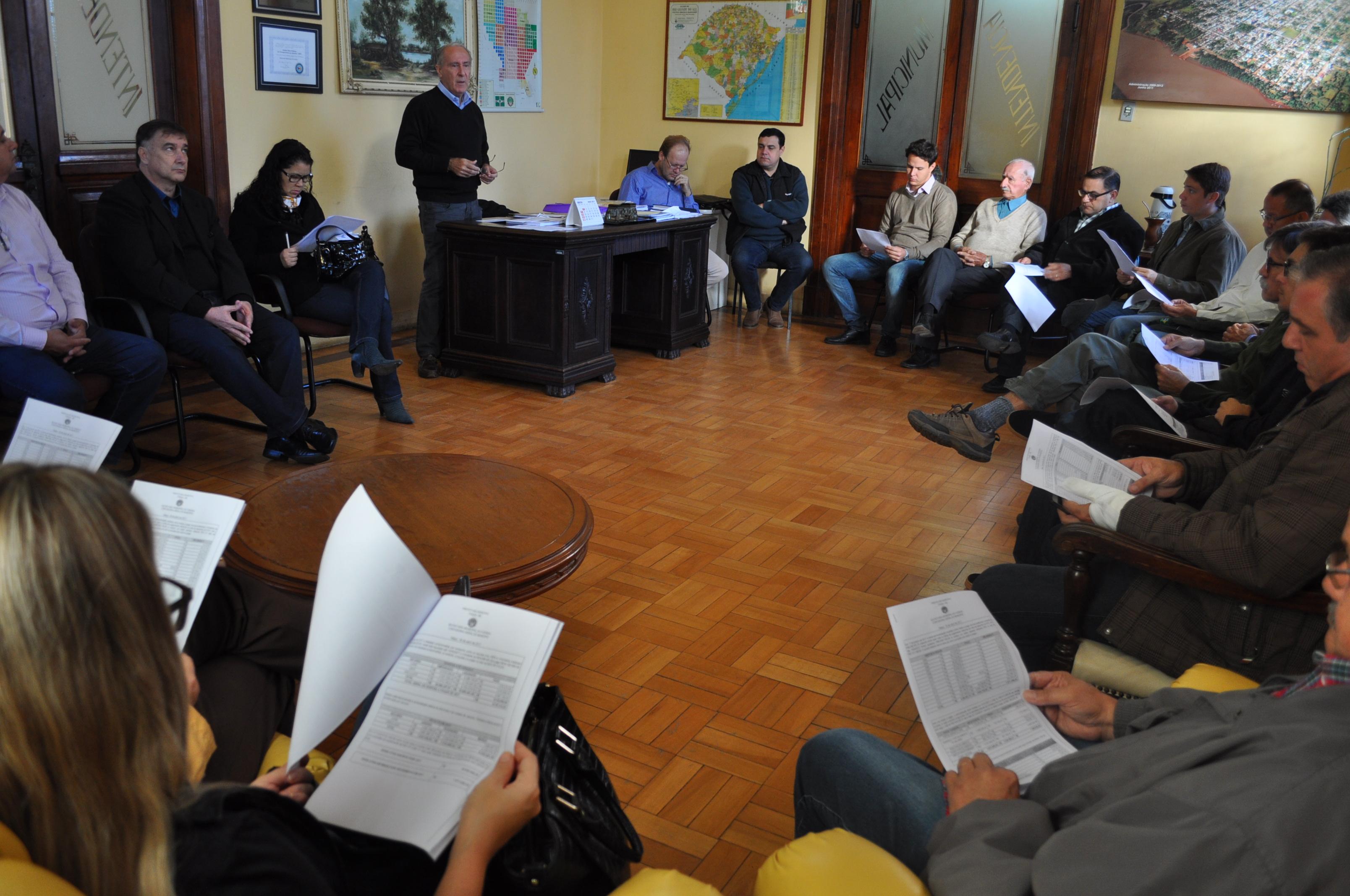 Prefeito apresentando relatório financeiro durante a reunião.