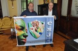 Ricardo (E) e Gil posam para foto segurando banner da CMJ