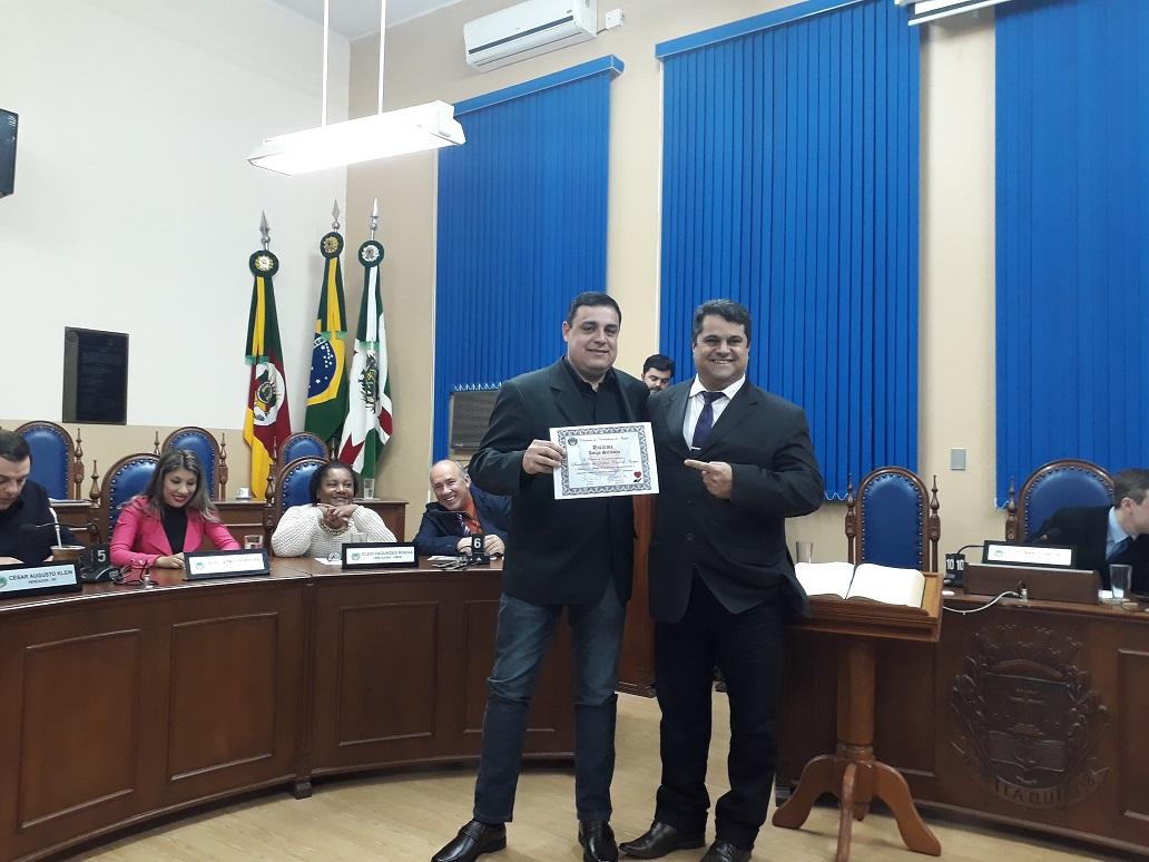 Roberto Zacouteguy recebendo diploma de 'amigo solidário' pela Defesa Civil e Serviços Urbanos