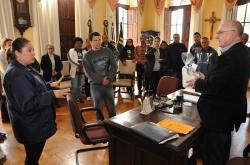 Graciela e Leandro, observados pelos demais usu�rios e profissionais do Centro, conversam com o prefeito ap�s a entrega da lembran�a