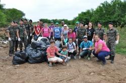 Participantes do mutirão posam para foto após recolherem lixo, entulhos e pneus velhos despejados irregularmente em via pública